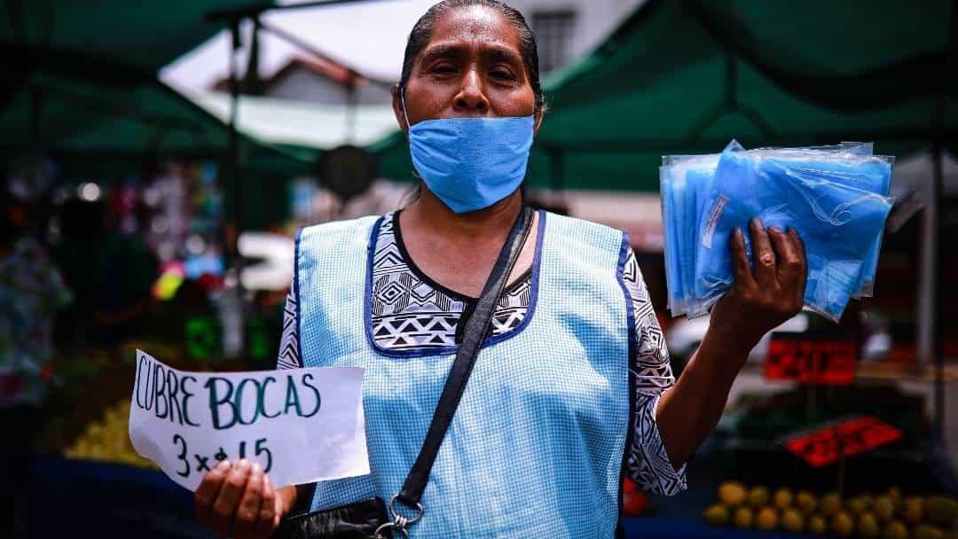 Ante la perdida de empleos, miles de mexicanos han visto en la venta de cubrebocas y gel antibacterial, el negocio ideal para seguir manteniendo ingresos, esta señora fue fotografiada en un tinaguis de la Gustavo A. Madero, CDMX