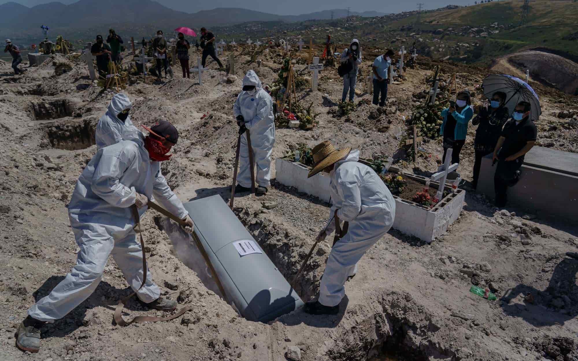 Trabajadores municipales de Tijuana, sepultan a persona muerta con síntomas de Covid-19 en un saturado panteón. Su familia ve el proceso de entierro guardando distancia. Foto: Los Ángeles Times